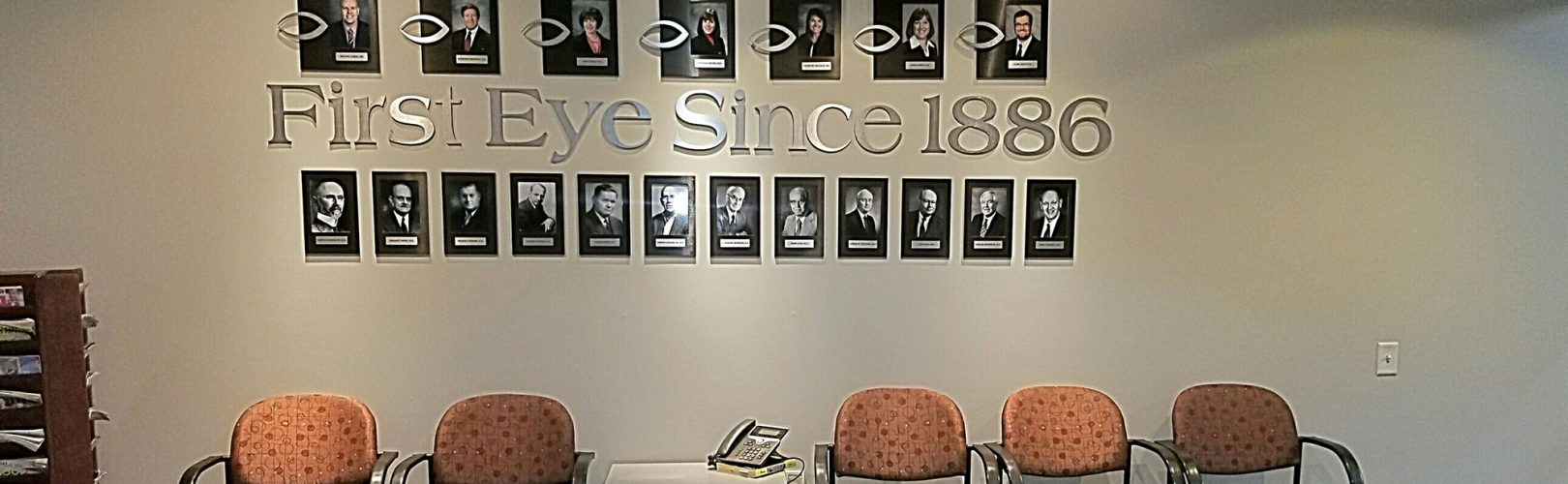 First Eye Associates waiting room with logo on the wall